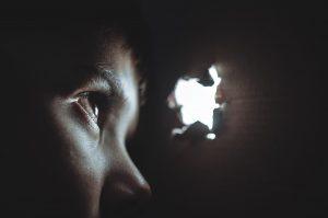 criança olhando pelo buraco em busca de justiça social